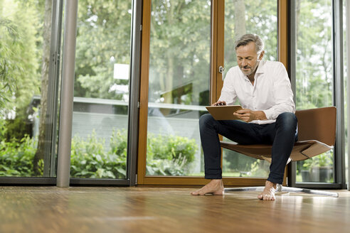 Barefoot man sitting on chair in his living room using tablet - SBOF000192