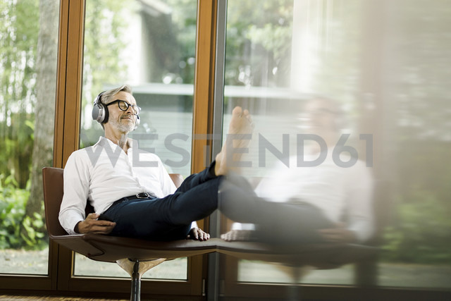 Man sitting on chair in his living room listening music with headphones - SBOF000198 - Steve Brookland/Westend61