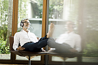 Man sitting on chair in his living room listening music with headphones - SBOF000198