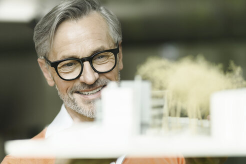 Portrait of smiling man looking at architectural model - SBOF000216
