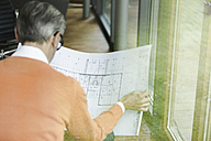 Back view of man looking at construction plan - SBOF000219