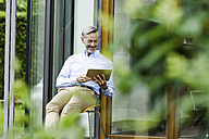 Man sitting on chair in front of his house using tablet - SBOF000231