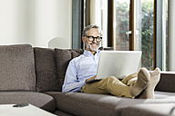 Smiling man sitting on couch in his living room using laptop - SBOF000240