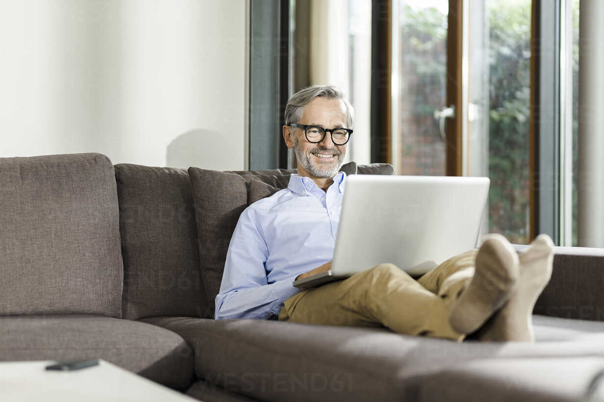 Smiling man sitting on couch in his living room using laptop - SBOF000240 - Steve Brookland/Westend61