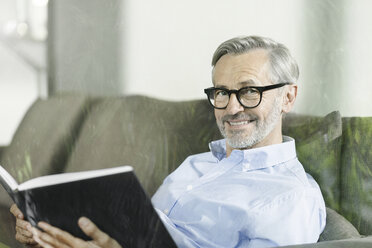 Portrait of smiling man sitting on the couch with book - SBOF000243