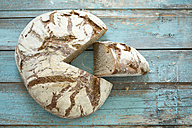 Rustic rye bread on blue wood - MAEF011985