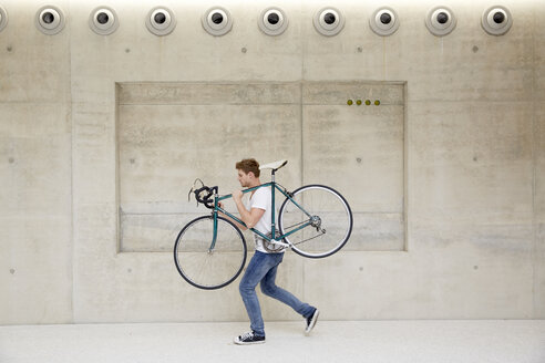 Young man carrying bicycle on his shoulder in front of concrete wall - FMKF003091
