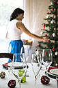 Laid table in dining room and woman decorating the Christmas tree - ABZF001036