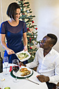 Woman serving mashed potatoes at Christmas dinner - ABZF001069