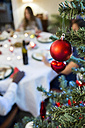 Christmas tree bauble and friends having Christmas dinner - ABZF001072