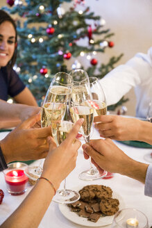 Friends toasting with champagne during a Christmas dinner - ABZF001075
