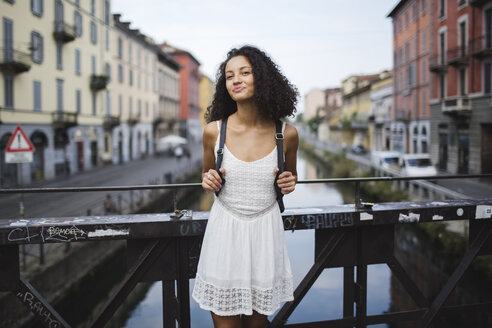Italy, Milan, portrait of smiling young woman with backpack wearing white summer dress standing on a bridge - MRAF000124