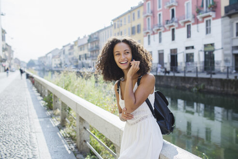 Italy, Milan, portrait of smiling young woman on the phone - MRAF000127