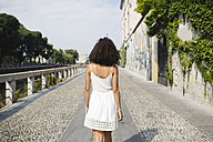 Back view of walking young woman wearing white summer dress - MRAF000130
