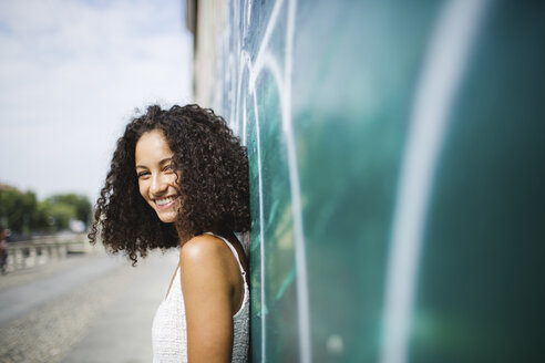Portrait of smiling young woman leaning against wall - MRAF000133