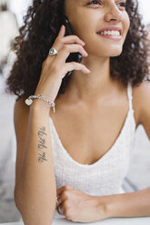 Smiling young woman with tattoo on forearm on the phone - MRAF000139