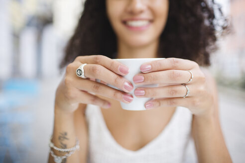 Hands of young woman holding cup of coffee, close-up - MRAF000145