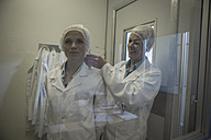 Two lab technicians putting on sterile protective clothing - ZEF010019