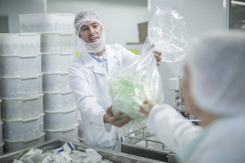 Lab worker in pharmaceutical plant handing over plastic bag - ZEF010040