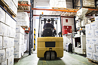 Worker driving forklift in warehouse - ABZF001094