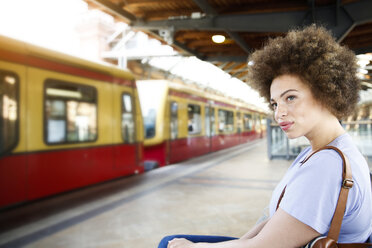 Young woman sitting on bench at train station - FK002058