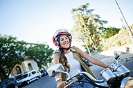 Happy young woman riding motorcycle - KIJF000733