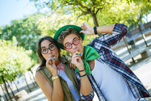 Young couple having fun with party blowers, joke glasses and caps - KIJF000736