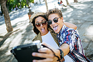 Young couple sticking out tongues while taking selfie with camera - KIJF000742