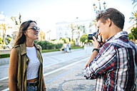 Spain, young man taking picture of his girlfriend - KIJF000754