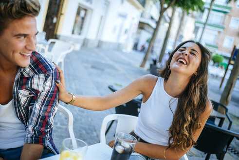 Young couple having fun at sidewalk cafe - KIJF000757