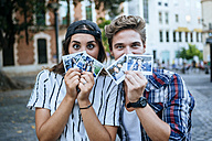 Young couple showing photographies of themselves - KIJF000775