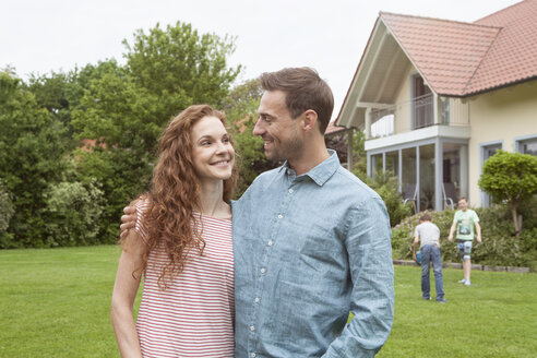 Smiling couple in garden with kids in background - RBF005081