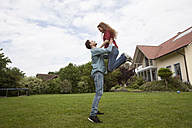 Happy man lifting up woman in garden - RBF005087