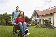 Man pushing smiling woman in wheelbarrow in garden - RBF005090