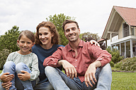 Portrait of smiling family sitting in garden - RBF005105