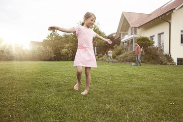 Girl dancing in garden with family in background - RBF005108