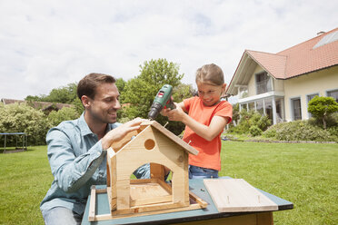 Father and daughter building up a birdhouse - RBF005117