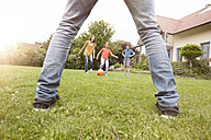 Family playing football in garden - RBF005123