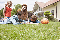 Smiling family in garden with football - RBF005126