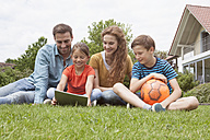 Smiling family sitting in garden with football using tablet - RBF005129