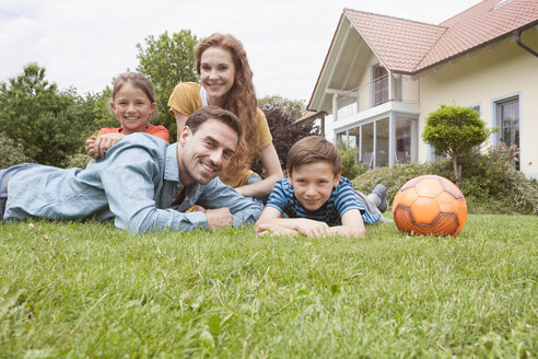 Portrait of smiling family in garden with football - RBF005132