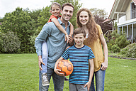 Portrait of smiling family standing in garden - RBF005135