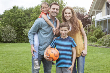Portrait of smiling family standing in garden - RBF005135