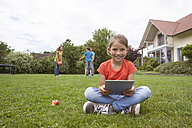 Smiling girl sitting in garden using tablet with family in background - RBF005138