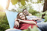 Smiling couple relaxing in hammock - RBF005144