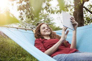 Smiling woman in hammock using tablet - RBF005147