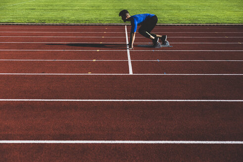 Runner on tartan track in starting position - UUF008291