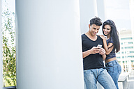 Smiling young couple outdoors looking at cell phone - SIPF000799