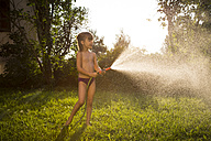 Little girl splashing water with garden hose - LVF005234