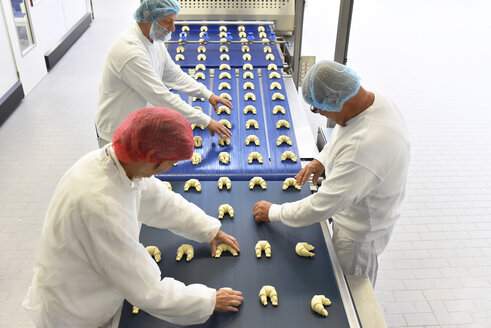 Workers at production line in a baking factory with croissants - LYF000530